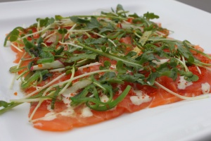 Salmon carpaccio with arugula and kaiware in yuzu dressing, seaweed, flying fish roe with wasabi mayo.